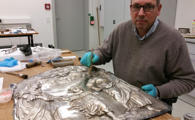 Uwe Schuchardt restauriert das silberne Antependium für die neue Sonderausstellung im Dommuseum Hildesheim. Foto: Bauerfeld / bph
